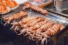 Il calamaro sugli spiedi sta grigliando da un venditore ambulante Immagini Stock