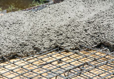 Il calcestruzzo bagnato è versato sul rinforzo dell'acciaio della rete metallica Immagine Stock