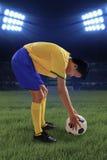 Il calciatore ha messo la palla sul campo Fotografia Stock