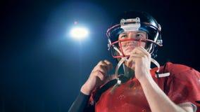 Il calciatore sta mettendo sul suo casco mentre era in un'arena di football americano archivi video