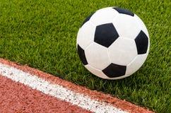 Il calcio è sul campo di calcio artificiale dell'erba nello stadio Immagine Stock Libera da Diritti
