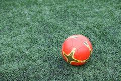 Il calcio arancio su erba verde Fotografia Stock Libera da Diritti