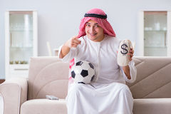 Il calcio di sorveglianza di sport dell'uomo arabo alla TV Fotografia Stock