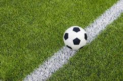 Il calcio di calcio sulla linea bianca nel campo di erba verde artificiale fotografia stock