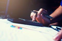 Il calcolatore di battitura a macchina della mano della donna con la penna di tenuta e calcola il fina Immagine Stock