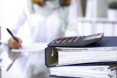 Il calcolatore ed i raccoglitori con le carte stanno aspettando per essere elaborati dalla donna di affari o dalla parte posterio Fotografia Stock Libera da Diritti