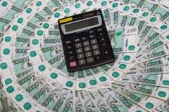 Il calcolatore nero si trova sulle banconote Immagine Stock Libera da Diritti