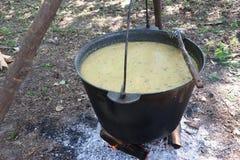 Il calderone con il porridge è cucinato su fuoco Immagine Stock