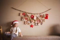 Il calendario di arrivo che appende sulla parete piccole sorprese dei regali per i bambini Ragazza che osserva alla destra fotografia stock libera da diritti