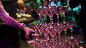 Il cameriere ha riempito la piramide della fontana del champagne dei vetri Bottiglia di champagne che è versato in una piramide d fotografia stock libera da diritti