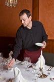 Il cameriere maschio organizza i piatti immagini stock