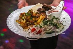 Il cameriere porta i piatti con le patate, la carne, l'insalata e la salsa immagine stock libera da diritti