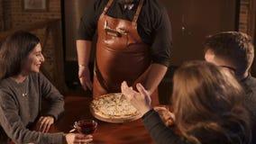 Il cameriere porta la pizza ad un gruppo archivi video
