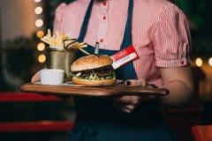 Il cameriere porta un hamburger immagine stock