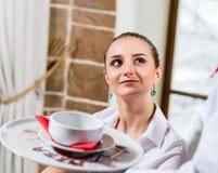 Il cameriere porta un piatto per una donna piacevole Immagine Stock