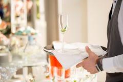 Il cameriere sta tenendo un vassoio con vetro di champagne fotografia stock