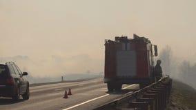 Il camion dei vigili del fuoco con un pompiere sulla strada estingue un incendio forestale, fumo pesante, il pericolo video d archivio
