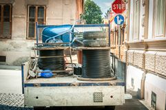 Il camion del carico in pieno degli strumenti ed i cavi ottici sotterranei rotolano per Internet parcheggiato sulla via per il la fotografia stock libera da diritti