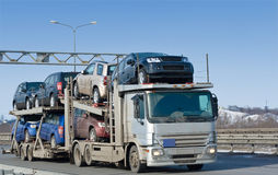 Il camion dell'elemento portante di automobile trasporta il nuovo batch automatico al commerciante Fotografie Stock Libere da Diritti