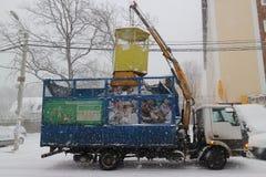 Il camion di immondizia funziona durante le precipitazioni nevose Fotografia Stock Libera da Diritti
