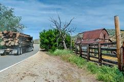 Il camion di Loggin in pieno dei ceppi passa un'azienda agricola nell'Idaho Fotografie Stock