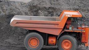 Il camion guida sotto l'escavatore, che carica il carico nel corpo Autocarri con cassone ribaltabile di estrazione mineraria nell stock footage