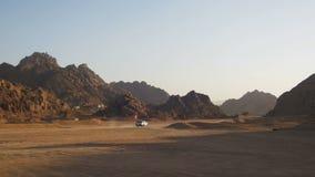 Il camioncino si muove attraverso il deserto nell'Egitto, sulla sabbia e sul fondo delle montagne video d archivio