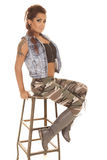 Il camo dei tatuaggi della donna si siede lo sguardo Fotografia Stock