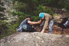 Il campeggiatore aiuta un altro per scalare la roccia immagine stock libera da diritti