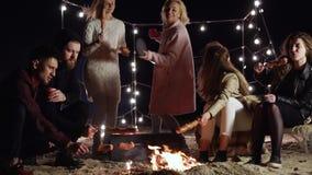 Il campeggio, amici riposa con le bevande e le salsiccie sugli spiedi su fondo delle lampade di ardore nella sera tirano