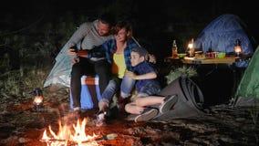 Il campeggio, giovani genitori con il bambino nel campo di viaggio fa la foto, la madre ed il padre di selfi con il figlio fotogr archivi video