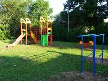 Il campo da gioco per bambini bei Le oscillazioni, gli scorrevoli e l'altro spettacolo stanno aspettando i bambini in questo post fotografia stock