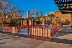 Il campo da gioco per bambini con le oscillazioni e gli scorrevoli che albeggiano in Corralillo de San Miguel a La Mancha, Spagna Fotografia Stock