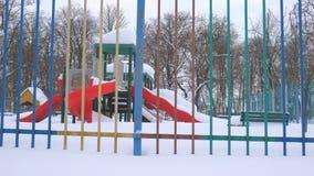 Il campo da gioco per bambini in forte nevicata stock footage