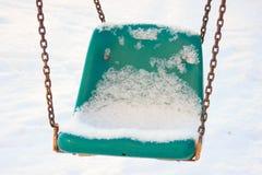 Il campo da gioco per bambini in inverno, oscillazioni e caroselli sotto la neve un giorno soleggiato nessuna gente, area vuota,  fotografia stock libera da diritti