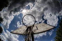 Il campo da pallacanestro anziano, canestro, ha strappato il reticolato contro il cielo Fotografia Stock Libera da Diritti