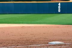 Il campo di baseball mostra la parete del fuoricampo e della prima base Immagini Stock Libere da Diritti