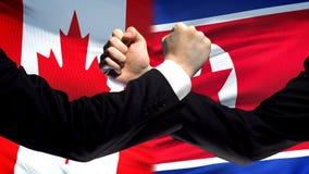 Il Canada contro confronto della Corea del Nord, pugni sul fondo della bandiera, diplomazia fotografia stock libera da diritti