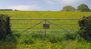 Il cancello nel campo che mostra un privato impedice di entrare il segno Immagine Stock