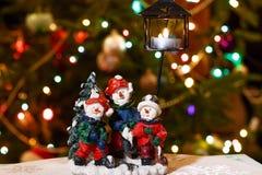 Il candeliere allegro dei pupazzi di neve con la candela bruciante davanti all'albero di Natale si accende Fotografia Stock