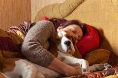 Il cane dorme sul letto con la padrona immagine stock