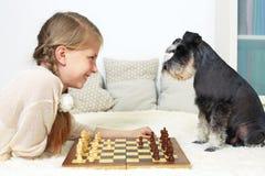 Il cane insegna al bambino a giocare gli scacchi Il vostro movimento Immagini Stock