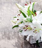 Il canestro bianco con il giglio bianco fiorisce il mazzo sulla t di legno rustica Fotografie Stock
