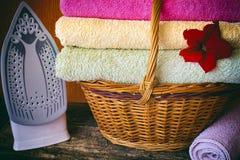 Il canestro con gli asciugamani colorati fiorisce, riveste di ferro, filtro da vignettatura sui precedenti di legno Immagine Stock Libera da Diritti