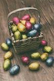 Il canestro della paglia ha riempito di uova di cioccolato di Pasqua avvolte in stagnola variopinta Fotografia Stock