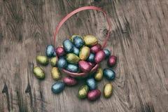 Il canestro della paglia ha riempito di uova di cioccolato di Pasqua avvolte in stagnola variopinta Fotografie Stock