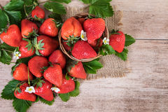 Il canestro delle fragole fresche con le foglie sulla vista superiore del fondo d'annata della fragola matura fruttifica Fotografia Stock