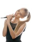 Il canto abbastanza biondo della donna dei giovani in microfono ha isolato vicino su karaoke immagini stock libere da diritti