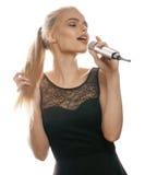 Il canto abbastanza biondo della donna dei giovani in microfono ha isolato vicino sul vestito nero, ragazza di karaoke Fotografia Stock Libera da Diritti