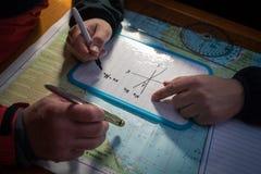 Il capitano del ` s della nave progetta l'itinerario su una mappa Fotografia Stock Libera da Diritti
